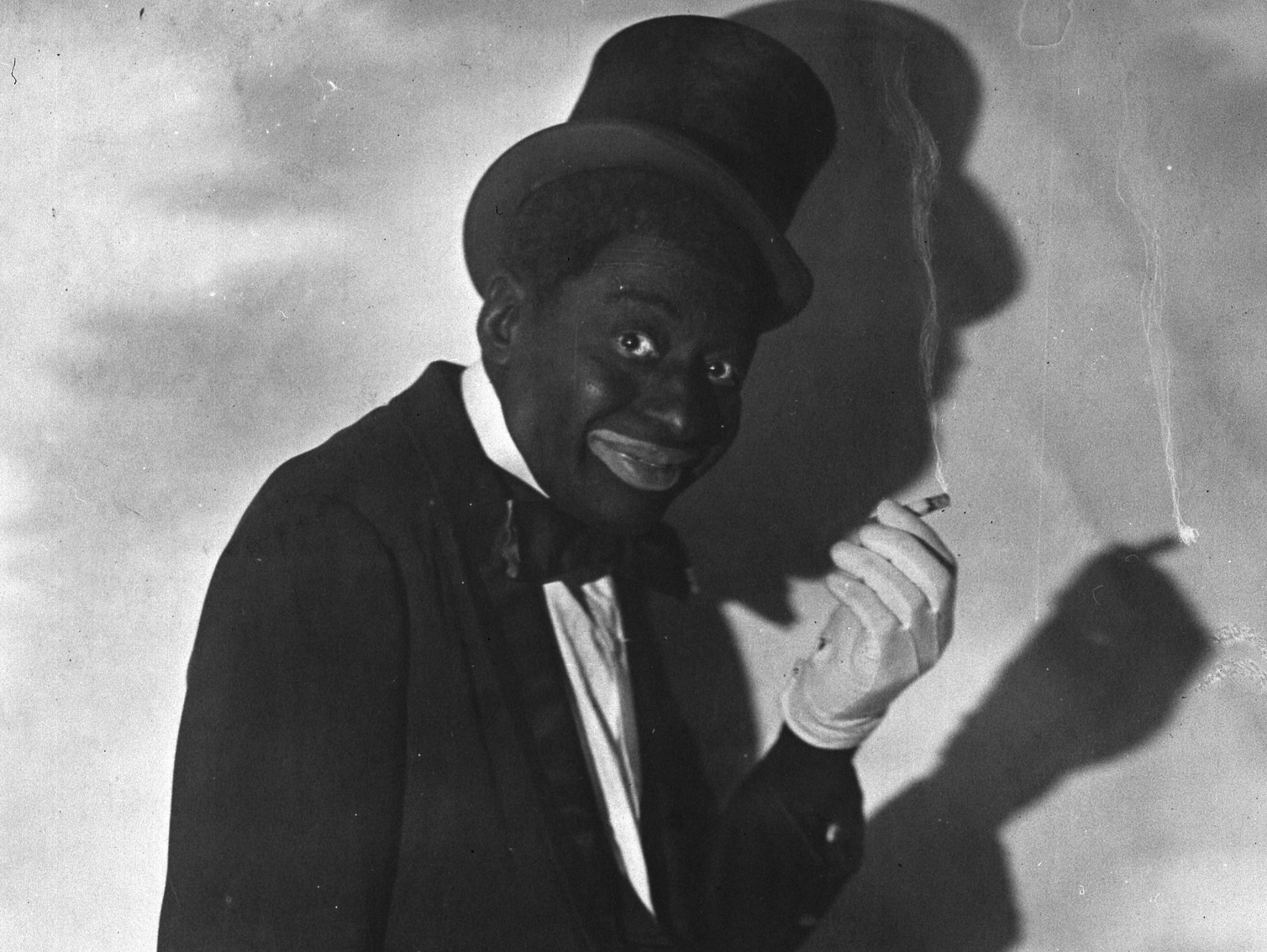 Photo portrait of Vaudeville star Bert Williams in blackface with cigarette; cropped from original. Promotional photo by Samuel Lumiere studio, New York City, via Library of Congress LC-USZ62-64924