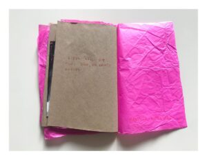 Zdjęcie otwartego zina. Lewa strona jest z brązowego papieru, na niej odręczny napis wykonany czerwonym długopisem. Prawa strona jest z różowego pogniecionego papieru, na niej odręczny napis wykonany czerwonym długopisem.