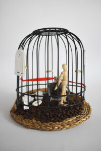 Na okrągłej słomianej plecionej podstawce stoi czarna klatka, w niej rozsypane są ziarna kawy, na nich stoi drewniana figurka człowieka