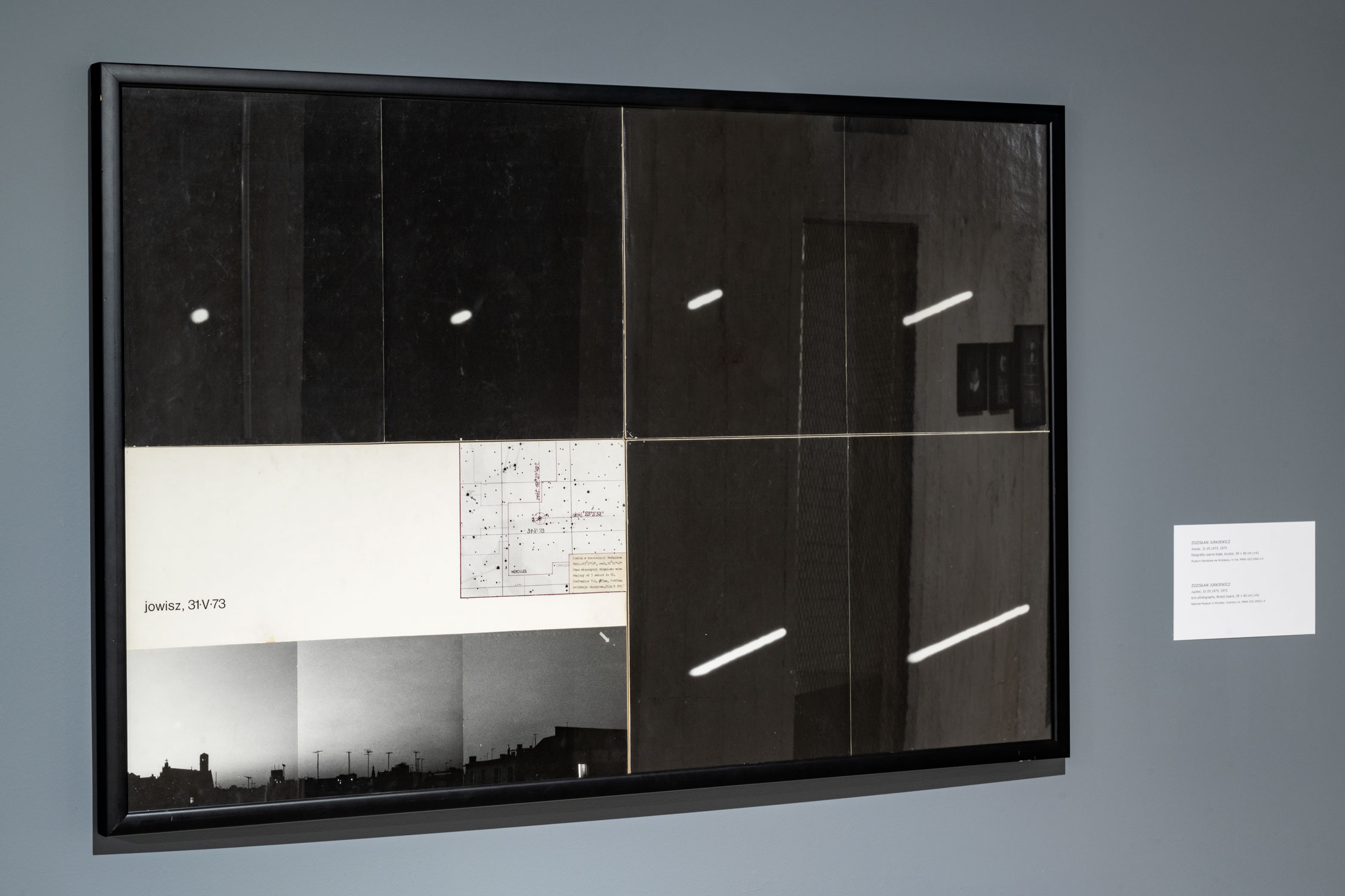 Praca Zdzisława Jurkiewicza Jowisz, 31.05.1973. Cztery poziome czarno-białe fotografie ułożone w dwóch rzędach po dwie w czarnej ramie na szarej ścianie.