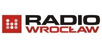 """Logo Polskiego Radia Wrocław. Na białym tle z lewej strony czerwony kwadrat, a w nim osiem białych kropek w trzech kolumnach, po trzy, po dwie i po trzy. Po prawej stronie u góry czarny napis dużymi literami """"radio"""", pod nim czerwony napis dużymi literami """"Wrocław""""."""